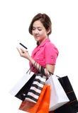 Zakupy kobiet mienia azjatykci szczęśliwi uśmiechnięci torba na zakupy kredytową kartą odizolowywającą na białym tle Obrazy Stock