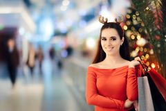 Zakupy kobieta Jest ubranym Bożenarodzeniowego renifera Uzbrajać w rogi kapitałkę Zdjęcie Royalty Free
