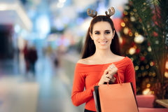 Zakupy kobieta Jest ubranym Bożenarodzeniowego renifera Uzbrajać w rogi kapitałkę Zdjęcia Stock