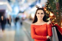 Zakupy kobieta Jest ubranym Bożenarodzeniowego renifera Uzbrajać w rogi kapitałkę Obrazy Royalty Free