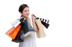 Zakupy kobiety mienia azjatykci szczęśliwi uśmiechnięci torba na zakupy odizolowywający na białym tle Fotografia Stock