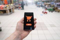 Zakupy kosz na telefonu komórkowego ekranie Guzika zakup Ręki mienia telefon komórkowy na supermarket plamy tle zdjęcia royalty free
