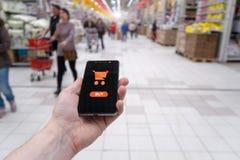 Zakupy kosz na telefonu komórkowego ekranie Guzika zakup Ręki mienia telefon komórkowy na supermarket plamy tle obrazy stock