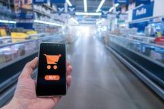 Zakupy kosz na telefonu komórkowego ekranie Guzika zakup Ręki mienia telefon komórkowy na supermarket plamy tle fotografia royalty free