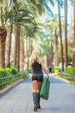 Zakupy, sprzedaż Piękna młoda blondynki dziewczyna trzyma zielonego papieru pakunki na ulicie obrazy royalty free