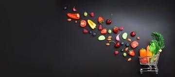 Zakupy tramwaj wypełniał z świeżymi organicznie warzywami, owoc i jagodami na czarnym chalkboard, Odgórny widok jarosz obraz royalty free