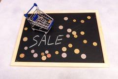 Zakupy tramwaju stojak na blackboard z monetami i teksta ` sprzedaży ` Fotografia Royalty Free