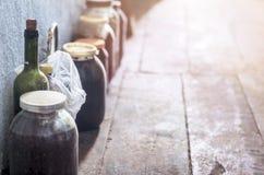 Zakurzeni słoje dżem z Plastikowymi nakrętkami, wino butelka z korkiem Zakrywającym z pająk siecią Wykładającą Wzdłuż Malującej G obraz stock