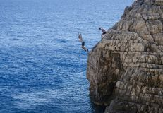 People jumping from cliff royalty free stock photos