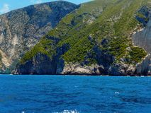 Zakynthos rocky shores. Beautiful vegetated mountain in water Stock Image