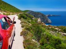 ZAKYNTHOS wyspa, GRECJA, JUN, 06, 2016: Piękny perspektywiczny widok na czerwonym samochodzie na drodze z ładną dziewczyną, Ag Io Fotografia Royalty Free