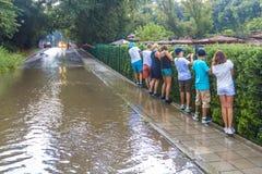 Zalewający po ulewnego deszczu, turyści obchodzą kałużę wzdłuż krawędzi chodniczek, podążać each inny w rzędzie, trzyma na ogrodz obrazy royalty free