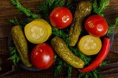 Zalewy: ogórkowi pomidory, zucchini i ziele, rozpraszali na drewnianym tle Fotografia Royalty Free