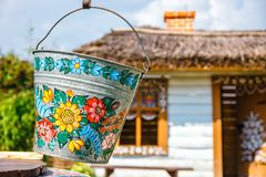 A bucket over a well in the colorful village - Zalipie, Poland. It is known for a local custom. Zalipie, Poland, August 19, 2018: A bucket over a well in the stock photos