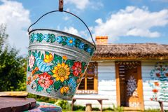 Zalipie, Poland, August 19, 2018: A bucket over a well in the colorful village - Zalipie, Poland. It is known for a local custom. Of painting the cottages with stock photography