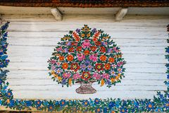 Zalipie, Poland, August 19, 2018: Close up of colorful flowers painted on wooden cottage in Zalipie, Poland. It is known for a lo. Cal custom of painting the royalty free stock photo