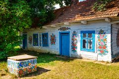 Zalipie, Poland, August 19, 2018: Colourful house with flowers painted on walls and sundial in the village of Zalipie, Poland. It. Is known for a local custom royalty free stock photos