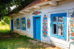 Colourful house with flowers painted on walls and sundial in the village of Zalipie, Poland. It. Zalipie, Poland, August 19, 2018: Colourful house with flowers royalty free stock images