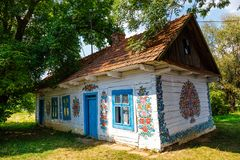 Colourful house with flowers painted on walls and sundial in the village of Zalipie, Poland. It. Zalipie, Poland, August 19, 2018: Colourful house with flowers royalty free stock photo