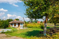 Colourful house with flowers painted on walls and sundial in the village of Zalipie, Poland. It. Zalipie, Poland, August 19, 2018: Colourful house with flowers stock photos