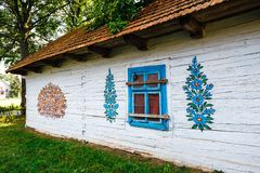 Zalipie, Poland, August 19, 2018: Colourful house with flowers painted on walls and sundial in the village of Zalipie, Poland. It. Is known for a local custom royalty free stock image