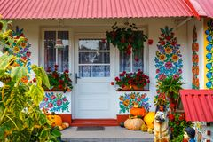 Zalipie, Poland, August 19, 2018: Colourful house with flowers painted on walls and sundial in the village of Zalipie, Poland. It. Is known for a local custom stock image