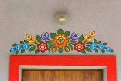 Painted facade of house decorated with a hand painted colorful flowers, Zalipie, Poland. ZALIPIE, POLAND - AUGUST 2, 2018: Painted facade of house decorated with stock photos