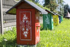 Painted old wooden beehives decorated with a hand painted colorful flowers, Zalipie, Poland. ZALIPIE, POLAND - AUGUST 3, 2018: Painted old wooden beehives stock photos