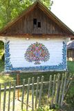 Painted old wooden cottage decorated with a hand painted colorful flowers, Zalipie, Poland. ZALIPIE, POLAND - AUGUST 2, 2018: Painted old wooden cottage royalty free stock photography