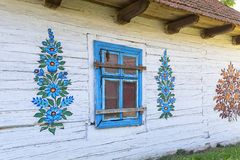 Painted old wooden cottage decorated with a hand painted colorful floral motives, folk art, Zalipie, Poland. ZALIPIE, POLAND - AUGUST 2, 2018: Painted old wooden stock photo