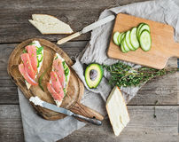 Zalm, avocado en thymesandwiches in baguette klopten met decoratiekabel op een rustieke houten raad over ruwe houten achtergrond Royalty-vrije Stock Foto's
