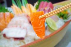 Zalm in eetstokjes met Japanse sashimireeks stock foto