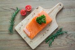 Zalmfilet op houten raad met tomatenrozemarijn en peterselie Stock Afbeeldingen