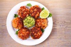 Zalmpasteitjes of cakes, kalk en avocado op witte plaat Fritters van vissen Salmon Burgers stock foto's