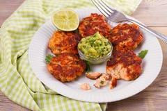 Zalmpasteitjes of cakes, kalk en avocado op witte plaat Fritters van vissen Salmon Burgers Stock Fotografie