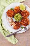 Zalmpasteitjes of cakes, kalk en avocado op witte plaat Fritters van vissen Salmon Burgers Royalty-vrije Stock Afbeeldingen