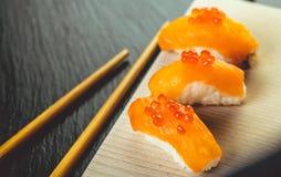 Zalmsushi en eetstokjes stock afbeelding