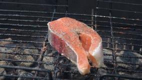 Zalmvissen op een grill Het roosteren van lapjes vlees van zalmforel de rode vissen stock video