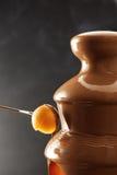 Zamaczać melonową piłkę w czekoladowego fondue fotografia royalty free