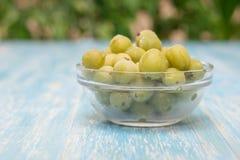 Zamarznięci jagoda agresty w pucharze szkło na rocznika stole Zdjęcie Stock