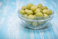 Zamarznięci jagoda agresty w pucharze szkło na rocznika stole Zdjęcia Stock