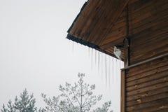 zamarznięci sople na dachu drewniany dom, najwyższe piętro drewniany dwór Lodowata pogodowa zimy scena zdjęcia stock