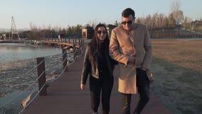 Zamarznięta ale szczęśliwa para w miłość spacerach wzdłuż nabrzeże zapasu materiału filmowego wideo zbiory