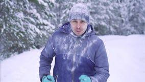 Zamarznięta męska atleta biega przez śnieżnego lasu, zimy aktywność zbiory