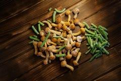 Zamarznięte dzikie pieczarki i fasolki szparagowe na drewnianym naturalnym backgr zdjęcie stock
