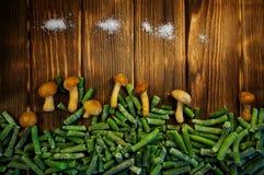 Zamarznięte grzyb pieczarki, fasolki szparagowe i sól na drewnianym backgr, zdjęcie stock