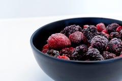 Zamarznięte jagody w czarnym pucharze na bielu ukazują się Obrazy Royalty Free