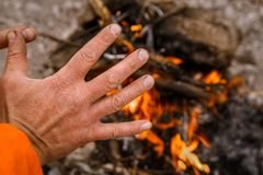 Zamarznięte męskie ręki grżą nad ogniskiem zdjęcie stock