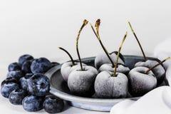 Zamarznięte wiśnie na zamarzniętych czarnych jagodach na kuchennym stole i talerzu obraz stock