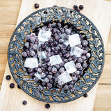 Zamarznięty czarny rodzynek z kawałkami lód na rocznika talerzu Zdjęcie Stock